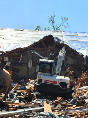 In this Sept. 17, 2017, photo, a worker uses machinery to clear away debris from Rockport First Assembly of God Church in Rockport, Texas. The church was hit by Hurricane Harvey.