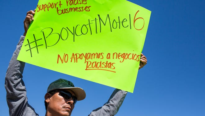 Marco Hernandez protests in front of a Motel 6 in Phoenix on Sept. 15, 2017. According to protesters, Motel 6 provided information about its guests to Immigration and Customs Enforcement.
