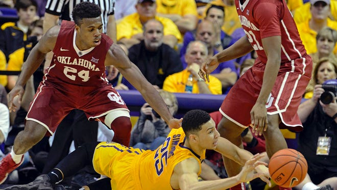 LSU forward Ben Simmons (25) loses the handle while hitting the floor as Oklahoma guard Buddy Hield (24) and Oklahoma forward Dante Buford (21) defend Saturday in Baton Rouge.