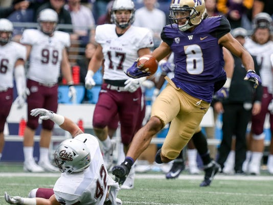 Washington's Dante Pettis returns a punt for a 67-yard touchdown as Montana's Josh Buss (42) falls to the turf during an NCAA college football game in Seattle on Saturday, Sept. 9, 2017.. (Kevin Clark/The Herald via AP)