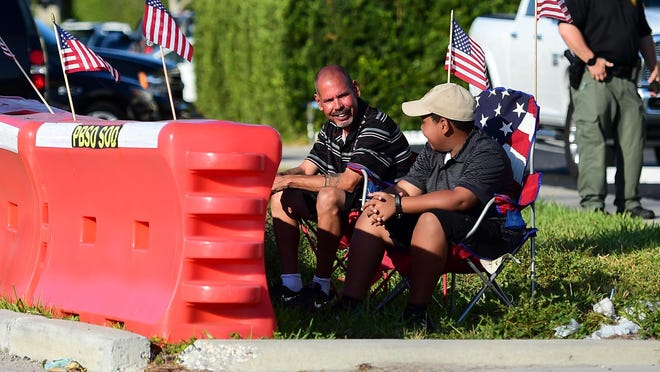 Trump supporter Steven Malaret and his son Manny of West Palm Beach wait for the presidential motorcade to pass as they wait on Southern Blvd. on Sunday, Dec. 1, 2019 in Palm Beach, Fla.
