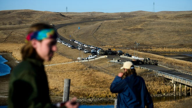 Two Dakota Access Pipeline protesters overlook a law enforcement barricade on N.D. Highway 1806 near Cannon Ball, N.D. on Saturday, Nov. 12, 2016.