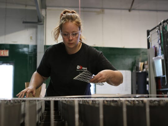 Emily Cramble, 29, checks the quality of parts that just came out of a fiber-optic laser machine E.J. Ajax in Fridley, Minn.