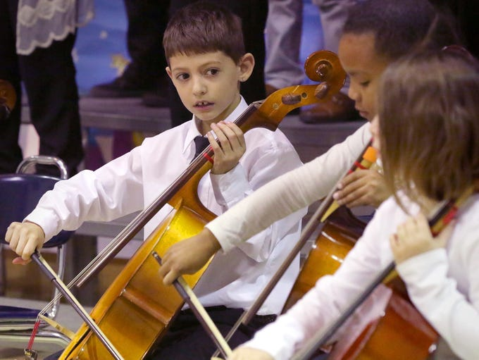 Zachary Bressler watches his fellow cellist during