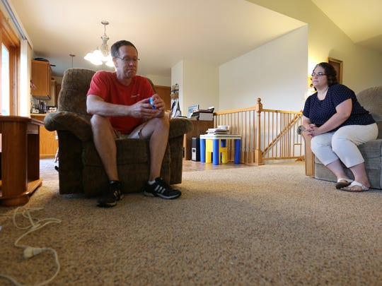 Mark and Jenny Knutson sit inside the living room of their Manitowoc home. Mark has begun applying to jobs after learning this month that his job at the Manitowoc Company is being moved out of state.