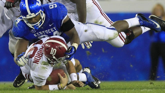 University of Kentucky's Za'Darius Smith (94) tackles University of Alabama quarterback AJ McCarron (10) during the first half of play at Commonwealth Stadium in Lexington, Kentucky.       October 12, 2013
