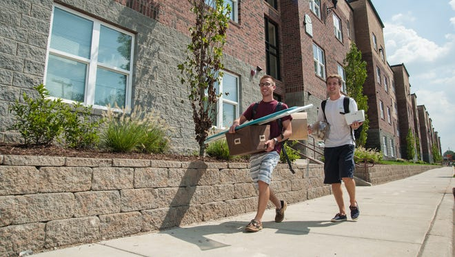 Retuning sophomores Nick Grueninger, 19, left, and Mitch Sirianno, 19, carry in belongings on their way to their fourth floor apartment after being moved from and unfinished room on Saturday. Campus Crest Communities Inc. continues to work on University of Louisville's newest student housing project as students move into rented rooms at The Grove on South Fourth Street. August 25, 2014