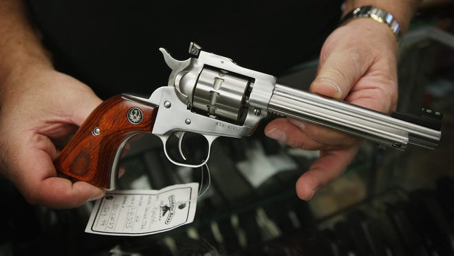 Fred Lutger, owner of Freddie Bear Sports, shows a Ruger Single Ten .22-caliber revolver being offered for sale at his store in Tinley Park, Ill.