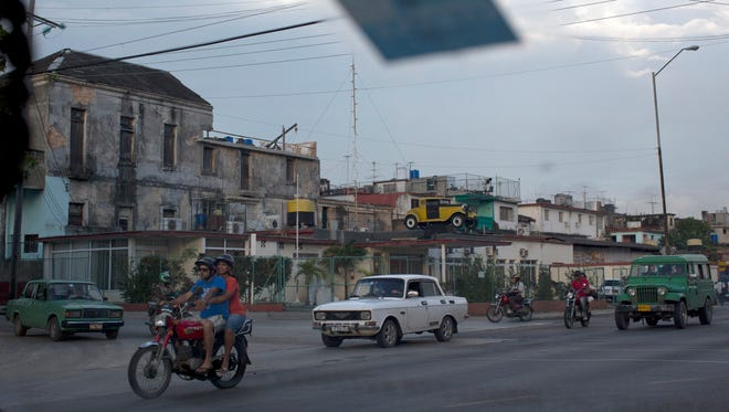 Motorcycles, Russian-made Ladas and a U.S.- made Willy jeep, right, drive along a street in Havana, Cuba, on Feb. 5, 2014.