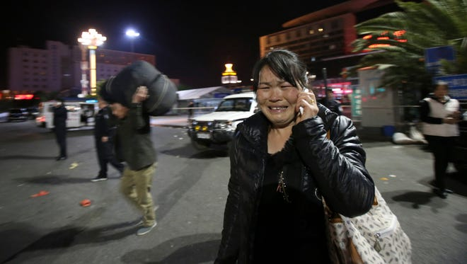 A woman reacts, at the crime scene outside a railway station after an attack, in Kunming, in southwestern China's Yunnan province, on March 1, 2014.