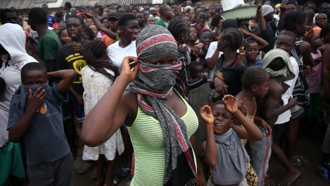 A crowd enters the grounds of an Ebola isolation center in the West Point slum Aug. 16 in Monrovia, Liberia.