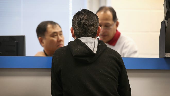 Abel Hernandez (C) applies for a Temporary Visitors Driver's License (TVDL) at a driver services facility in Chicago, Illinois.