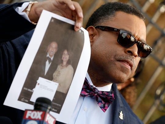 Arnold E. Reed, attorney for former U.S. Rep. John Conyers, D-Detroit, holds up a photo of Conyer's accuser Marion Brown from the 2011 Barristers Ball outside Conyer's house on Dec. 1, 2017, in Detroit.