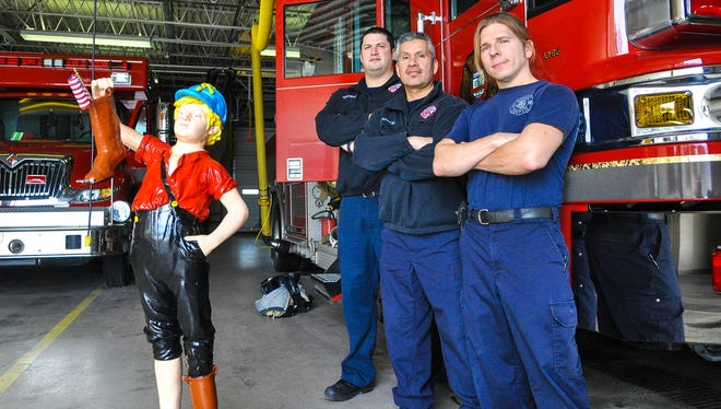 Stevens Point firefighters Victor Kedrowski, right, Armando Ramon and Ross Oestreich all appeared in the department's 2012 calendar which raised money for various causes, including preserving the Boy and the Leaky Boot statue, seen here. The statue was stolen early Saturday.