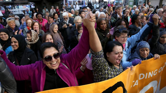 Women of several faiths hold hands at the Women Led Interfaith Prayer Service at Fountain Square on Dec. 16. Tyler Barrott writes to say he is following the example of his Nazi-fighting great-grandfather in standing with Muslims.