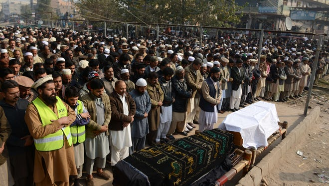 Mourners attend a funeral on Wednesday for victims of an attack by Taliban militants at a military-run school in Peshawar, Pakistan.