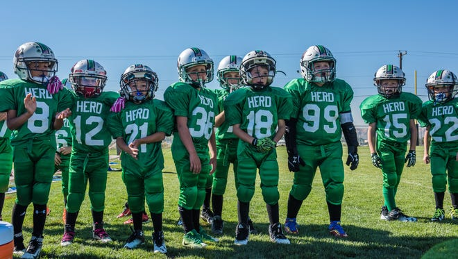 Players with the Four Corners Young American Football League's Farmington Herd team participate Sept. 17 in a ribbon-cutting ceremony for the Kirtland Youth Association's new football field.