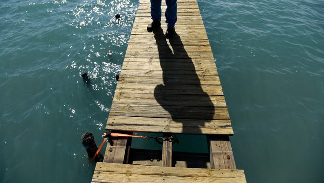 A piece of dock is missing as Chuck Hahn talks about the damage caused by high water levels and freighter traffic Friday, April 14, at his home on Harsens Island.