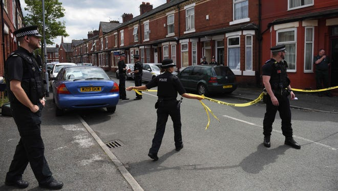 Police officers set a cordon outside the entrance of a property in the Moss Side area of Manchester on May 27, 2017 during an operation.