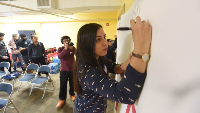 Nicole Romero, a Dreamer, signs a banner that will be delivered to Rep. Rodney Frelinghuysen's office, as   immigrant youth gather in December to share their stories and discuss why the Dream Act is important for New Jersey.