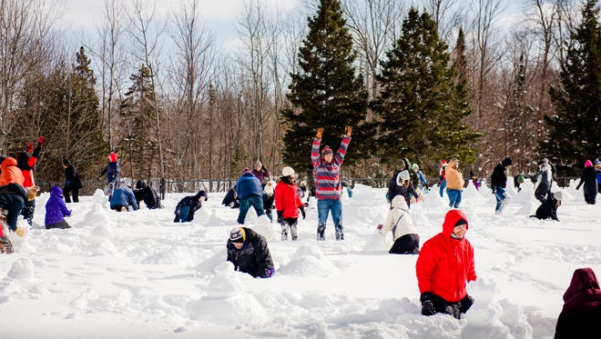 "Michigan Technological University students and community members build snowmen on MTU's Sherman Field. Participants in the event, dubbed ""Snowman Left Behind,"" built 2,228 snowmen in one hour, which the schools says bests the previous record of 2,036 set in Akabira, Japan, in 2015."