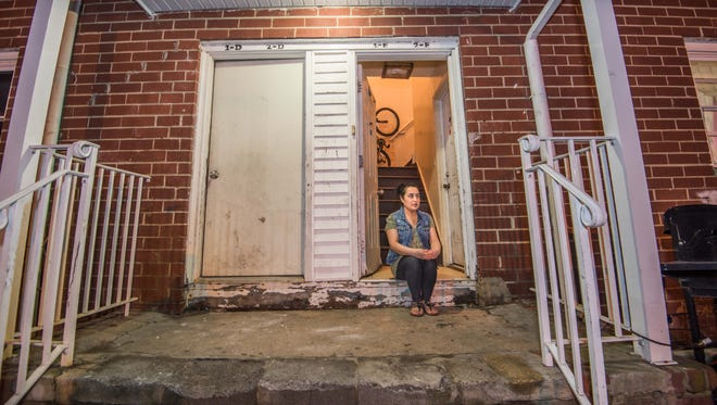 Rosario Atonal sits on the front step of her apartment building at the Cottage Manor Apartments in Lakewood. The front door is off its hinges, providing no security.
