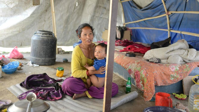 In this photograph taken on April 21, 2016, Nepalese earthquake survivor Menuka Rokaya cares for her child as she speaks with AFP in Ramechhap on the outskirts of Katmandu a year after a quake flattened her home in Nepal.