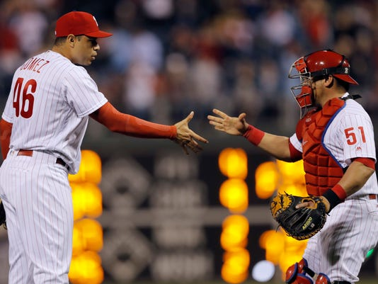 Philadelphia Phillies relief pitcher Jeanmar Gomez, left, and catcher Carlos Ruiz meet after they won a baseball game against the Cincinnati Reds, Friday, May 13, 2016, in Philadelphia. (AP Photo/Matt Slocum)