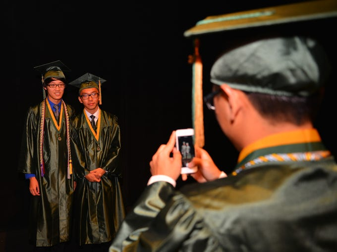 Melbourne Central Catholic held their 50th commencement ceremony at the  King Center Saturday morning, with 100% of the graduating class getting accepted into college. Eric Sun and Tommy Chen get photographed by Kevin Jiang.