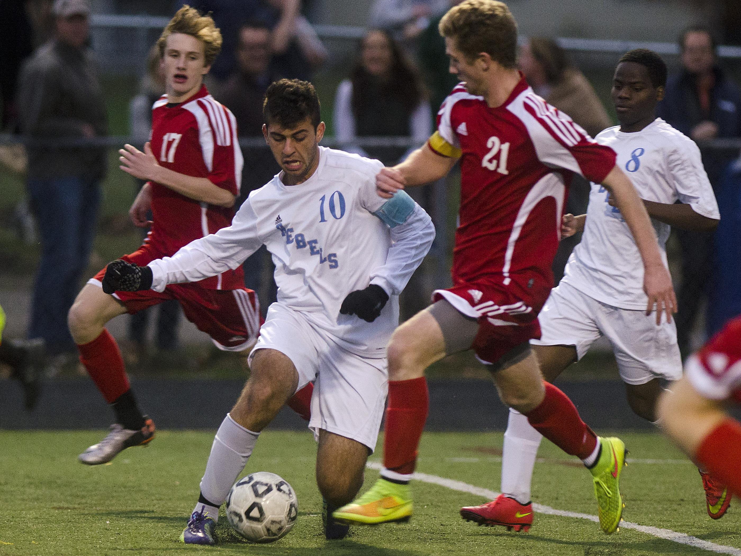 South Burlington's Ismail Temirov (10) attempts to dribble past Champlain Valley's Patrick McCue (21) during the second half of 2014 Division I boys soccer semifinal.