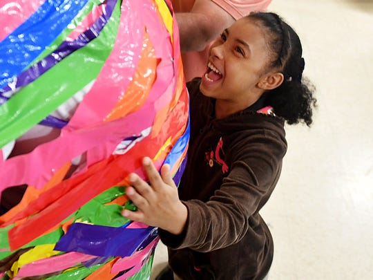 Andrew Jackson Elementary School 5th grader Khalasia Brown smiles at her principal, Ramonica Dorsey, as she places a strip of duct tape on her during a Relay for Life fund raiser, Friday, May 4. Students paid $1 for a strip of tape. Over $500 was raised to donate to Relay for Life.