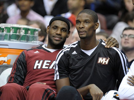 FILE - In this Oct. 30, 2013 file photo, Miami Heat's LeBron James, left, and Miami Heat's Chris Bosh are seen during the second half of an NBA basketball game against the Philadelphia 76ers on Wednesday, Oct. 30, 2013, in Philadelphia. igning day has arrived in the NBA, if the biggest free agents care to grab their pens. But it's unclear if Carmelo Anthony, Chris Bosh and Dwyane Wade _ who all might be waiting on LeBron James to go first _ are ready. (AP Photo/Michael Perez, File)