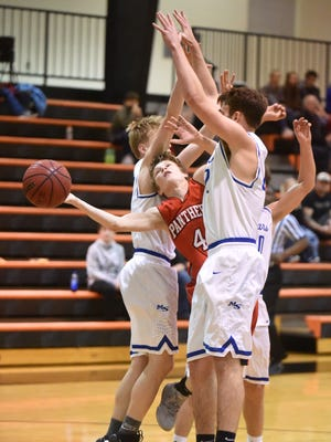 Norfork's Brett Sorters is sandwiched by Mammoth Spring's Alex Mero (left) and Sagen Godwin (right) during district tournament action Monday night at Calico Rock.