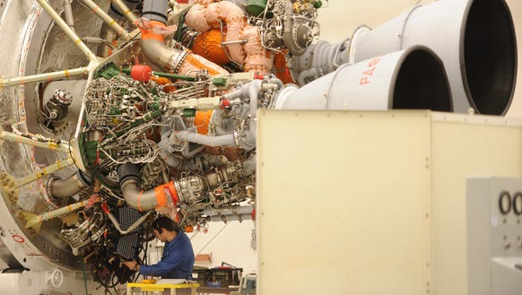 An Orbital employee looks over a rocket engine inside