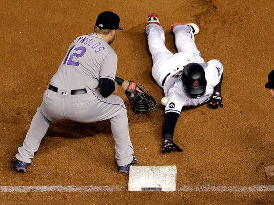 Arizona Diamondbacks' Jean Segura is hit on the arm on a pick-off attempt as Colorado Rockies' Mark Reynolds (12) can't make the catch during the fifth inning of a baseball game, Tuesday, Sept. 13, 2016, in Phoenix. (AP Photo/Matt York)