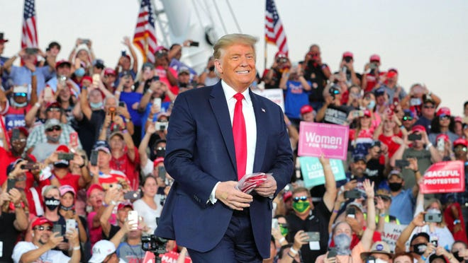 President Donald Trump responds to cheering supporters as he arrives Monday for a campaign rally at Orlando-Sanford International Airport in Florida.