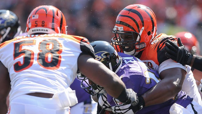 Cincinnati Bengals defensive tackle Geno Atkins wraps up Baltimore Ravens running back Javorius Allen as Carl Lawson closes during the 2017 home opener. The defensive linemen were part of a heavy rotation during the game.