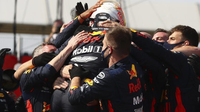 Red Bull driver Max Verstappen is mobbed by his team Sunday after winning the 70th Anniversary Formula One Grand Prix at Silverstone, England.
