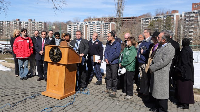 Yonkers Mayor Mike Spano and other officials talk Friday about a mudslide affecting the Walsh Road senior apartments shown in the background.