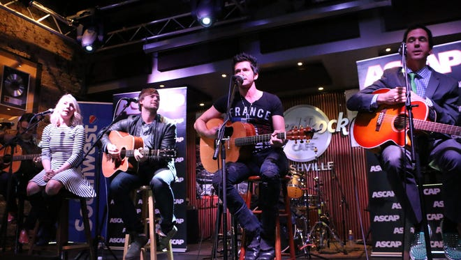 Michael Carter sings one of his hit songs while fellow songwriters RaeLynn (left), Jimmy Robbins, and J.T. Harding look on at Hard Rock Cafe Friday night as part of Tin Pan South.