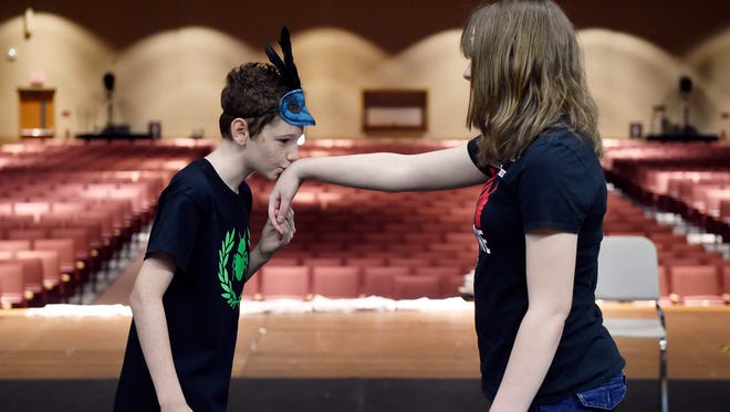 "Carter Lentz, 12, kisses the hand of Makayla Bledsoe, 14, as they perform as the eponymous Romeo and Juliet during a rehearsal of William Shakespeare's ""Romeo and Juliet"" at Dover Youth Shakespeare Academy at Dover Area High School."