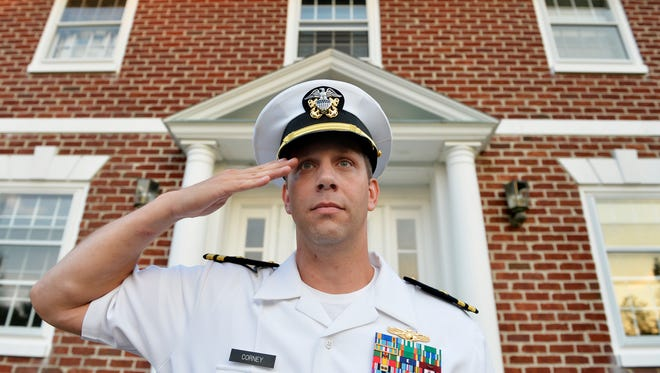 "Joshua Corney stands for a portrait outside his Glen Rock home in 2015. Corney, a lieutenant commander, was serving his 18th year in the U.S. Navy and had recently moved his family to Glen Rock, where he grew up. Until recently, Corney had played a recording of ""Taps"" outside his home every evening just before 8 p.m. in remembrance of military service members."