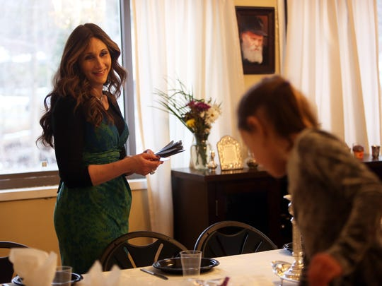 Bassie Friedman sets the table for Shabbat with her
