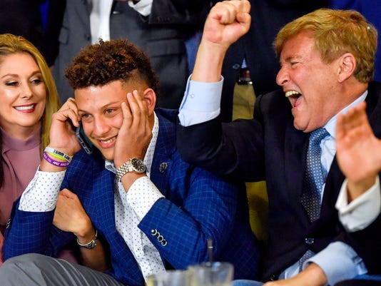 FILE - In this Thursday, April 27, 2017, file photo, from left, Randi Martin, Patrick Mahomes and Leigh Steinberg react while Mahomes is on a call with the Kansas City Chiefs, during an NFL football draft watch party in Tyler, Texas. When Kansas City Chiefs general manager John Dorsey and coach Andy Reid boldly jumped up 17 spots to select Mahomes with the 10th overall pick last week, they did so gambling that he will be their franchise quarterback long into the future. (Chelsea Purgahn/Tyler Morning Telegraph via AP, File)