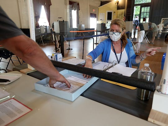 Volunteer Kelly Grech slides a ballot underneath a plastic partition to protect her from transmission of COVID-19 while helping out at town election on Saturday, June 27, 2020. Normally there would be two volunteers to check in residents but the town clerk applied for a waiver with the Secretary of State to reduce the number of poll workers at town election.