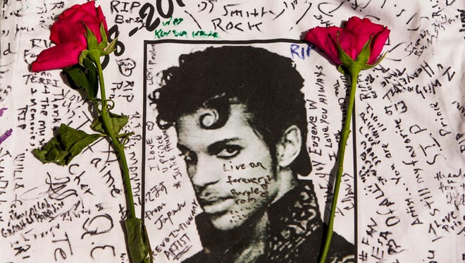 Flowers lay on a T-shirt signed by fans of singer Prince at a makeshift memorial place created outside Apollo Theatre in New York, Friday, April 22, 2016. The pop star died Thursday at the age of 57. (AP Photo/Andres Kudacki)