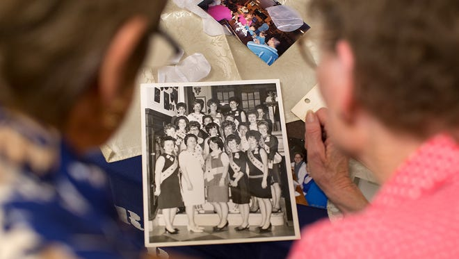 Linda Spahr of York, right, and Margie Sheffer of York  look at old photographs during a White Rose Mothers of Twins & Triplets Club meeting for the month of September. The group gets together to share tips and discuss issues confronting parents of multiples.