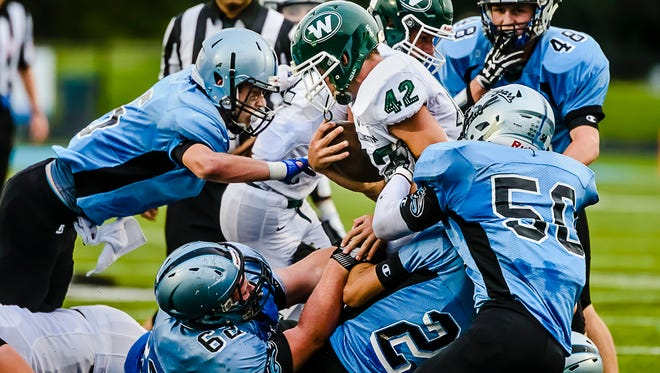 Tommy Dutcher ,42, of Williamston is brought down by several members of the Lansing Catholic defensive unit in the 1st quarter.
