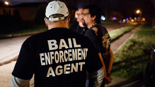Bail bondsmen wait to take a prisoner to jail on April 15, 2017, in Ankeny.