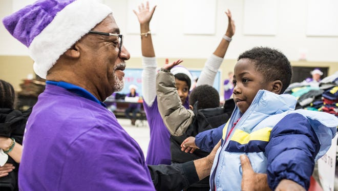 December 13, 2017 - Lawrence Bullard, with FedEx, helps Bryson Fleming, 4, pick a new jacket at A.B. Hill elementary school courtesy of Operation Warm and FedEx. FedEx supplied cash for coats and volunteers to hand them out during giveaways organized by 19-year-old Philadelphia-based nonprofit Operation Warm.